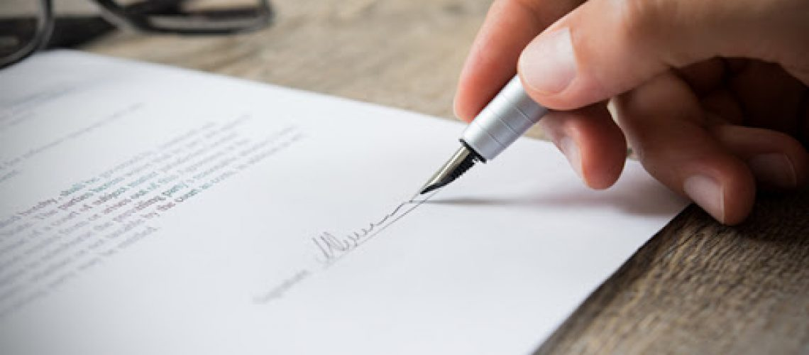 Close up of hand of businessman signing a form. Business man signing contract for future deal. Business man signing legal document. Male hand signing employee contract with a bond.